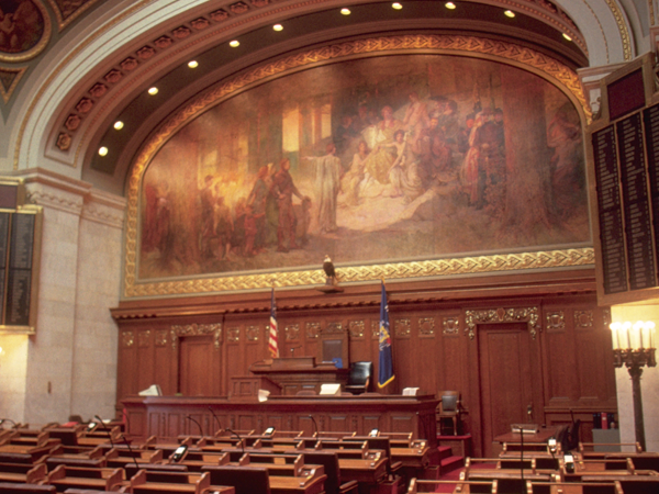 Wisconsin legislative sessions room facing the front of the room with the large mural above the leader's desk.