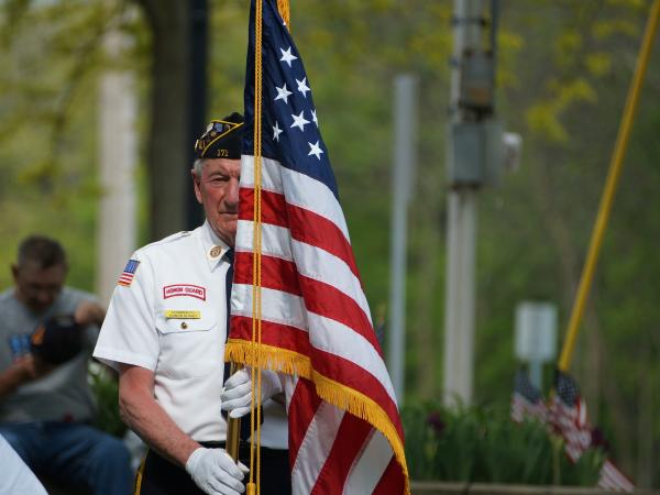 A veteran holding the American flag marching in a Memorial Day parade.