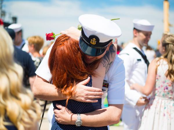 A navy officer hugging a woman with other soldiers and family greeting each other around them.