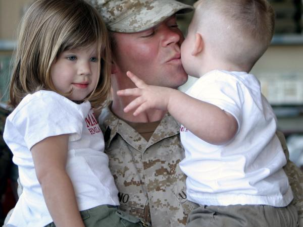 A soldier holding his two small children, giving the youngest a kiss.
