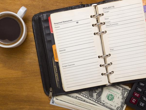 A planner opened to a page with Required Resources:  Person/telephone, Materials, Budget Expenses; and Projects:  Target, Start, Finish, Idea/Summary, Plan. This planner is on top of a calculator and a stack of money sitting next to a cup of coffee.