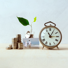 A stack of coins to the left of a glass jar of coins with a growing plant coming out of it, next to an alarm clock and a small picture in the middle front with a couple holding hands and walking on the beach.""