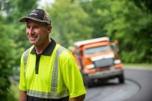 highway worker in front of truck