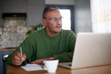 Green sweater older man at computer