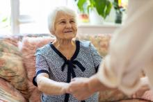 """""""elderly woman holding hands with caregiver"""""""