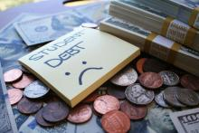 """A sticky note sitting over money with the words, """"STUDENT DEBT"""" and an unhappy face."""